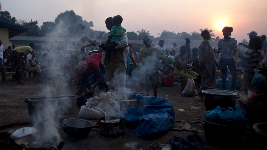 Smoke rises from wood fires, as displaced people prepare their evening meals, at a makeshift camp on a church ground in the Castor neighborhood of Bangui, Central African Republic, Saturday, Dec. 28, 2013. According to church officials, more than 40,000 people sleep at the site, many of them in the open air. More than 200,000 people are already displaced in the capital city, and people continue to arrive at camps across the city. (AP Photo/Rebecca Blackwell)