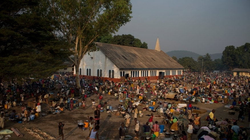 Displaced people camp out on a church ground in the Castor neighborhood of Bangui, Central African Republic, Saturday, Dec. 28, 2013. According to church officials, more than 40,000 people sleep at the site each night, many of them in the open air. More than 200,000 people are already displaced in the capital city, and people fleeing deadly sectarian violence continue to arrive daily at the makeshift camps. (AP Photo/Rebecca Blackwell)