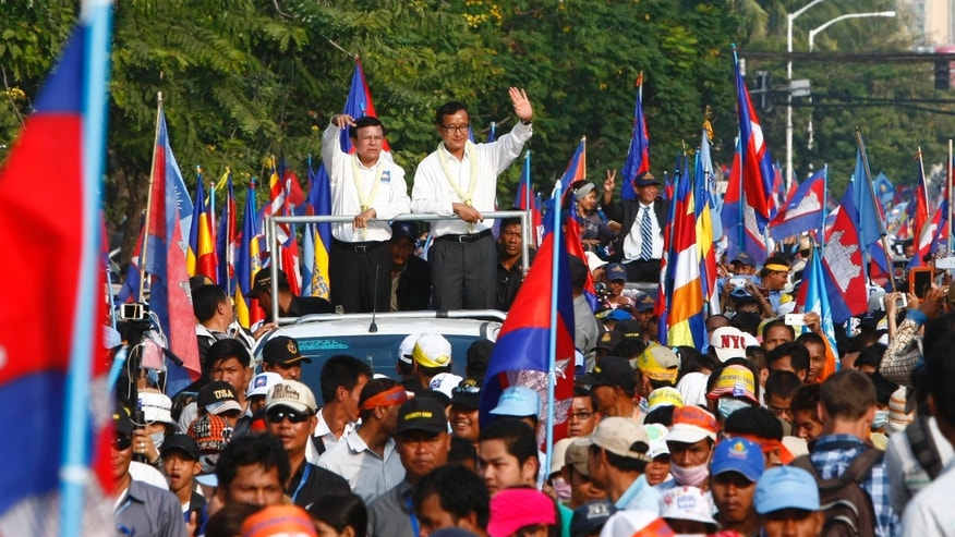 Cambodia's opposition leader Sam Rainsy, center right, and  his party Cambodia National Rescue Party's Vice President Kem Sokha, center left, wave during a mass demonstration at the on the main roads in Phnom Penh, Cambodia, Sunday, Dec. 29, 2013. In July, 2013,  Prime Minister Hun Sen won elections that extended his 28-year rule in the poor Southeast Asia nation, but protesters led by the head of the opposition, Sam Rainsy, accuse him of rigging the vote. They have been staging street protests and demanding that he resign and call new elections. (AP Photo/Heng Sinith)