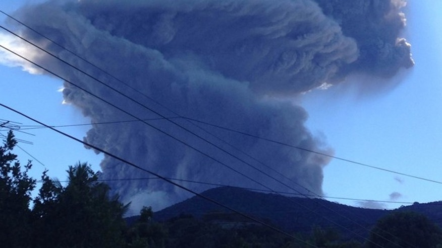 Dec. 30, 2013: The Chaparrastique volcano shoots a a cloud of gas and ash about three miles into the air as seen from the city of San Miguel, El Salvador.