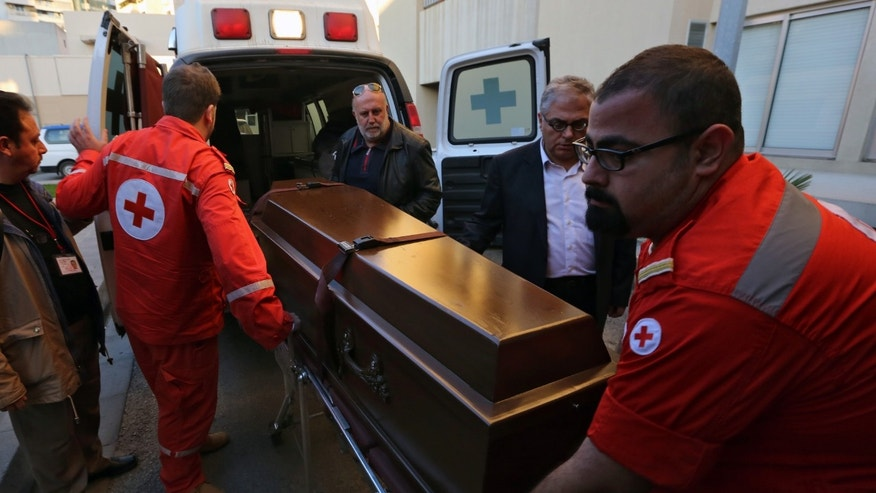Lebanese Red Cross workers carry the coffin of British doctor Abbas Khan, 32, who was seized by Syrian government troops in November 2012, into the Hotel-Dieu de France hospital in Beirut, Lebanon, Saturday, Dec. 21, 2013. The circumstances in which Khan, died while in detention in Syria remain in dispute. A senior British official has accused Syrian President Bashar Assad's government of effectively murdering Khan, while the Syrian authorities say the doctor committed suicide and there was no sign of violence or abuse. (AP Photo/Bilal Hussein)