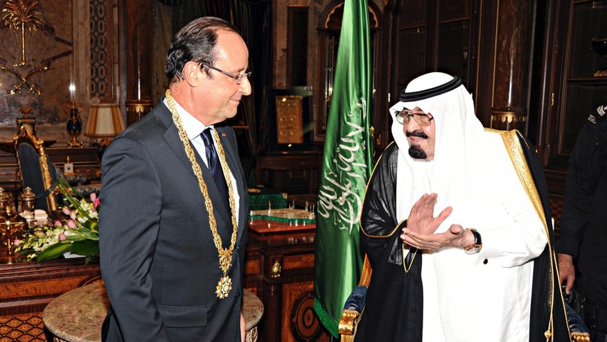 FILE-- In this Sunday, Nov. 4, 2012 file photo released by Saudi Press Agency, King Abdullah of Saudi Arabia, right, applauds French President Francois Hollande, left, after presenting him with the Order of Merit in Jiddah, Saudi Arabia. Increasingly vocal in its frustration over the United States' Mideast policies, Saudi Arabia is strengthening ties elsewhere, seeking out an alignment that will bolster its position after it was pushed to the sidelines this year.  It may find a solution in France, whose president is ending 2013 with 24 hours of high-level meetings with the Saudi leadership in a visit intended to showcase commercial and diplomatic strength. (AP Photo/SPA, File)
