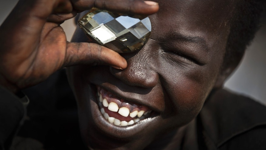 A displaced boy mimics the photographer taking a picture of him, using a fake plastic jewel, at a United Nations compound which has become home to thousands of people displaced by the recent fighting, in the capital Juba, South Sudan Sunday, Dec. 29, 2013. Some 25,000 people live in two hastily arranged camps for the internally displaced in Juba and nearly 40,000 are in camps elsewhere in the country, two weeks after violence broke out in the capital and a spiralling series of ethnically-based attacks coursed through the nation, killing at least 1,000 people. (AP Photo/Ben Curtis)