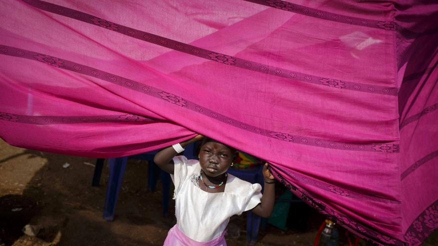 A young displaced girl peers out from her makeshift tent at a United Nations compound which has become home to thousands of people displaced by the recent fighting, in the capital Juba, South Sudan Sunday, Dec. 29, 2013. Some 25,000 people live in two hastily arranged camps for the internally displaced in Juba and nearly 40,000 are in camps elsewhere in the country, two weeks after violence broke out in the capital and a spiralling series of ethnically-based attacks coursed through the nation, killing at least 1,000 people. (AP Photo/Ben Curtis)