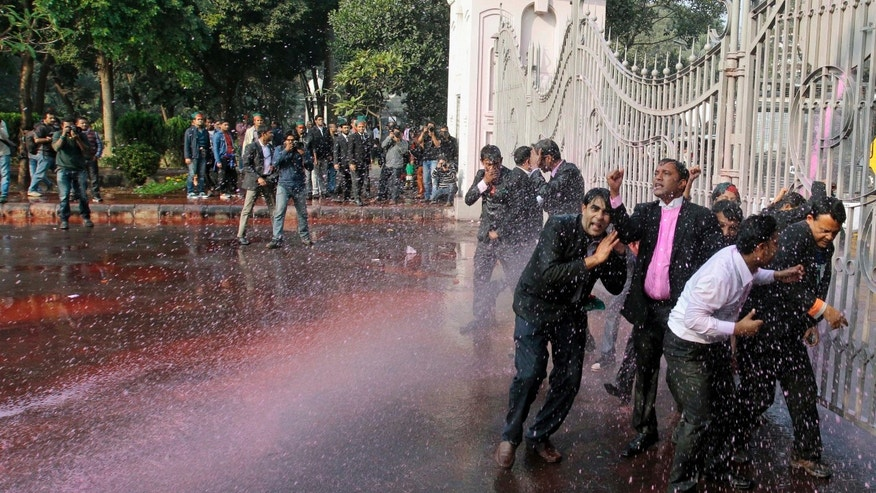 Opposition Bangladesh Nationalist Party (BNP) lawmakers are shot water cannon by police during a protest in Dhaka, Bangladesh, Sunday, Dec. 29, 2013. Security forces and opposition activists clashed in Bangladesh's capital on Sunday, leaving at least one person dead, as thousands of police took to the streets to foil a mass rally calling on Prime Minister Sheikh Hasina to cancel upcoming elections. (AP Photo/A.M. Ahad)