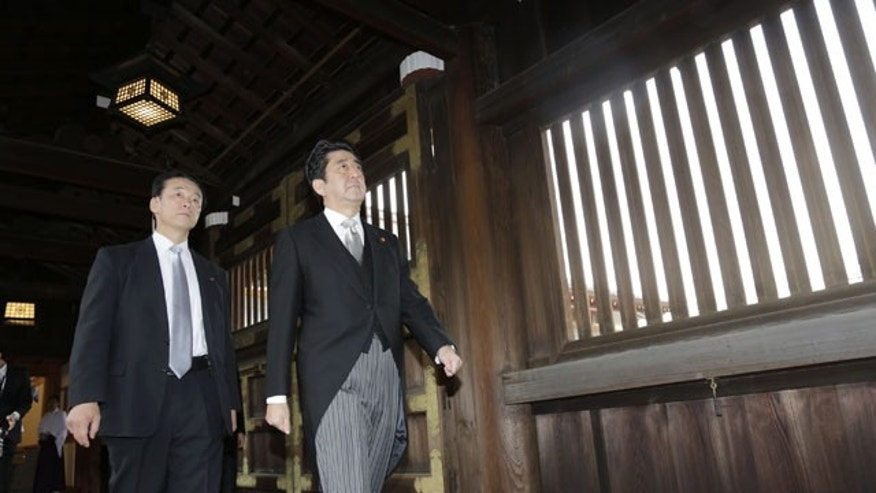 December 26, 2013: Japanese Prime Minister Shinzo Abe, followed by a security police officer, left, walks at Yasukuni Shrine to pay respect for the war dead, in Tokyo. (AP)