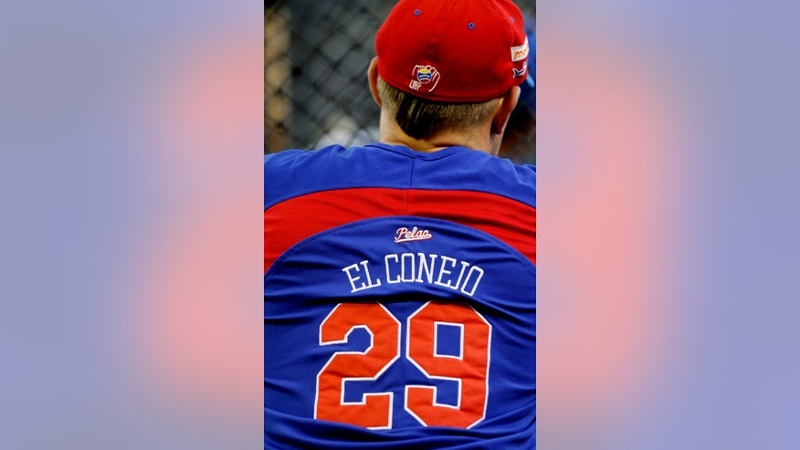 "In this Nov. 27, 2013 photo, C.J. Retherford, a 28-year-old Arizona native, wears a jersey with his nickname ""El Conejo,"" or ""the Rabbit"" during a warm-up before a the start of a baseball game at Estadio Universitario in Caracas, Venezuela. Last season Retherford played for the RedHawks of the sister cities of Fargo, North Dakota, and Moorhead, Minnesota. He now plays third base for the Tiburones, or Sharks, in the city of La Guaira outside Caracas, one of the nine ""imports"" the league allows each team to hire. (AP Photo/Fernando Llano)"