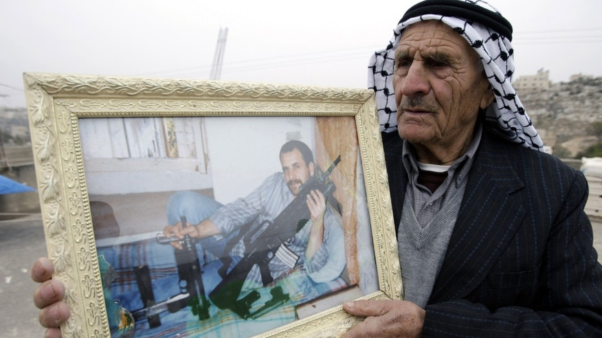 Palestinian Awad Kmail holds a picture of his son Ahmad at his home in the West Bank village of Kabatyeh near Jenin, Sunday, Dec. 29, 2013. Kmail is one of the 26 Palestinian prisoners who were convicted in connection to the killing of Israelis, that Israel announced to release this week. (AP Photo/Mohammed Ballas)