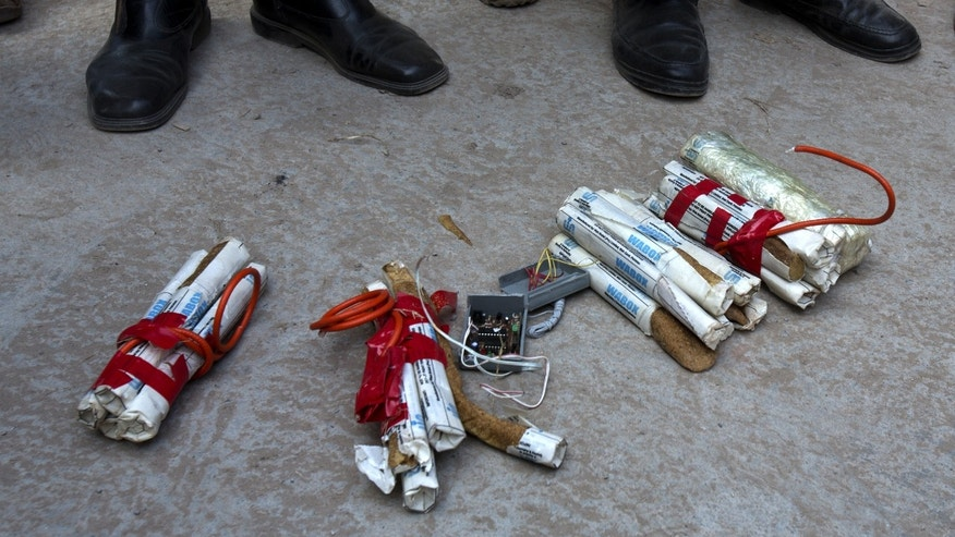 Pakistani police officers stand near explosive devices found close to the residence of Pakistan's former President Pervez Musharraf in Islamabad, Pakistan, Monday, Dec. 30, 2013. Musharraf will appear in a court on Jan 1, 2014 in a high treason case. (AP Photo/B.K. Bangash)