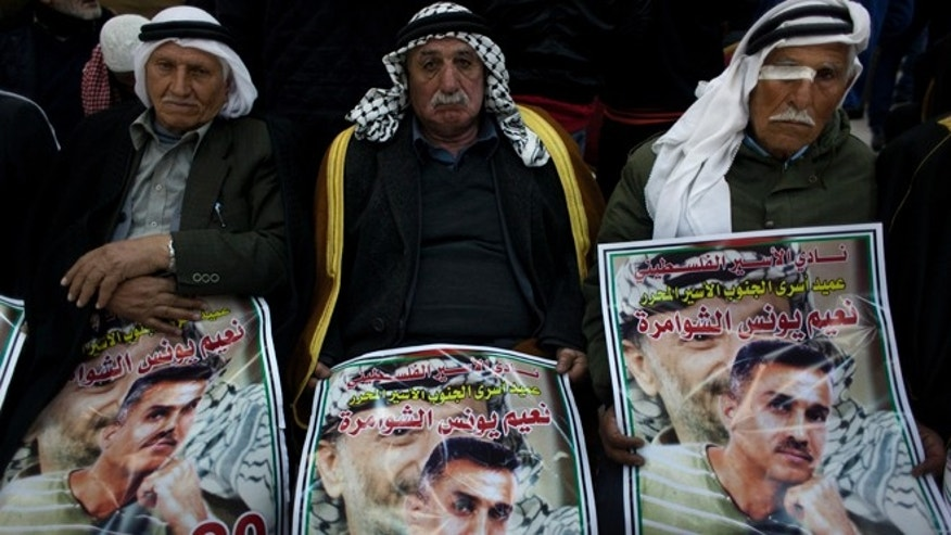 "Dec. 30, 2013: Elderly Palestinian men hold posters with pictures of released prisoner Na'em al-Shawamreh in Arabic that reads his name and ""the dean of the released prisoners, 20 years in captivity,"" during celebrations at the Palestinian headquarters in the West Bank city of Ramallah."