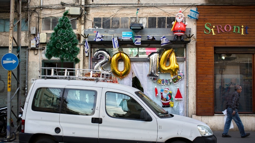 A man walks past a shop selling decorations ahead of New Years Eve in Tel Aviv, Israel, Monday, Dec. 30, 2013. In Israel, the somber, soul-searching and autumnal new year of the lunar Jewish calendar overshadows the Gregorian's Jan. 1. (AP Photo/Oded Balilty)