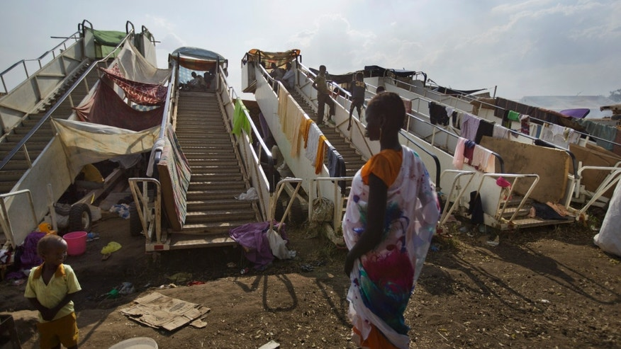 Moveable stairs used for passengers to board aircraft are repurposed into makeshift shelters by the displaced at a United Nations compound which has become home to thousands of people displaced by the recent fighting, in the capital Juba, South Sudan Sunday, Dec. 29, 2013. Some 25,000 people live in two hastily arranged camps for the internally displaced in Juba and nearly 40,000 are in camps elsewhere in the country, two weeks after violence broke out in the capital and a spiralling series of ethnically-based attacks coursed through the nation, killing at least 1,000 people. (AP Photo/Ben Curtis)