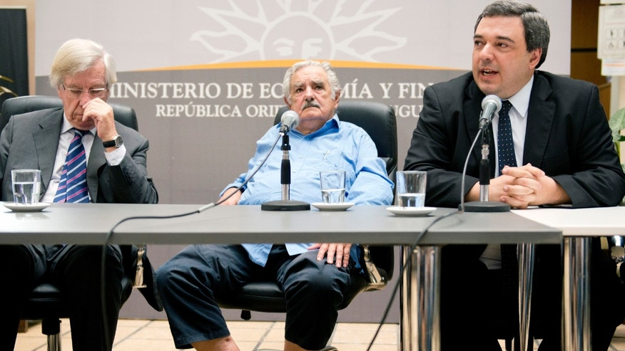 Uruguay's President Jose Mujica, center wearing sandals, sits between his Vice President Danilo Astori, left, and newly appointed Finance Minister Mario Bergara during Bergara's ceremony to assume office in Montevideo, Uruguay, Thursday, Dec. 26, 2013.  Former Finance Minister Fernando Lorenzo resigned last week in order to stand trial on charges related to the Uruguayan state airline Pluna. (AP Photo/Matilde Campodonico)