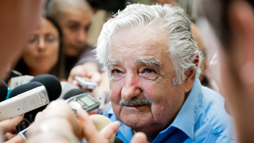 Uruguay's President Jose Mujica speaks to reporters after attending a ceremony for the newly appointed finance minister, in Montevideo, Uruguay, Thursday, Dec. 26, 2013. Finance Minister Fernando Lorenzo, resigned last week in order to stand trial on charges related to the Uruguayan state airline Pluna. (AP Photo/Matilde Campodonico)