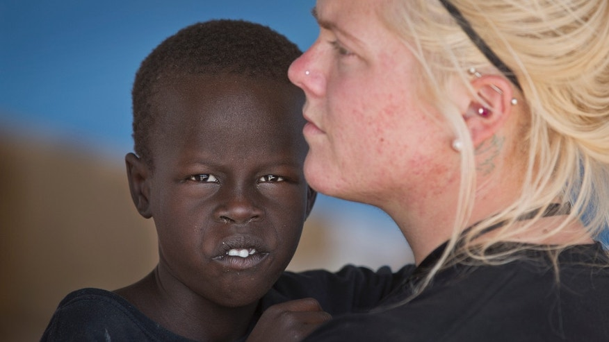 In this photo taken Monday, Dec. 30, 2013, American Katie Talbott, 23, holds one of the 10 orphans her mother Kim Campbell and stepfather Brad Campbell are raising, at the United Nations camp where they have taken shelter along with many other displaced people, in Malakal, South Sudan. Brad and Kim Campbell from Nebraska have been feeding, clothing, educating and parenting 10 South Sudanese children for nearly two years but now they are desperately seeking a way to protect them after their life was upended on Christmas Day when full-fledged war broke out where they live in Malakal, and everyone fled to seek shelter at a nearby U.N. base. (AP Photo/Ben Curtis)