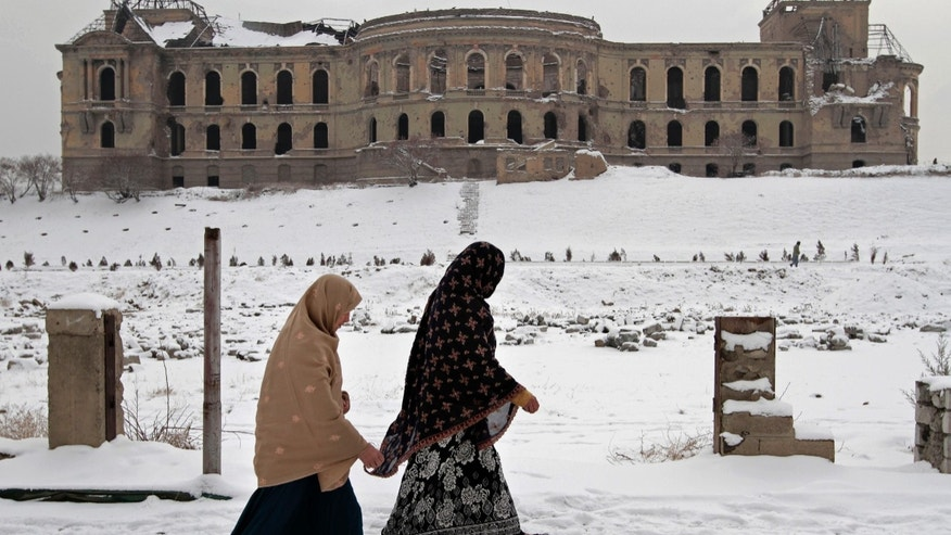Afghan women walk past the palace of the late King Amanullah Khan, which was destroyed during the civil war in early 1990s, in Kabul, Afghanistan, Monday, Dec. 30, 2013. Kabul has been experiencing below freezing weather and snow. (AP Photo/Rahmat Gul)