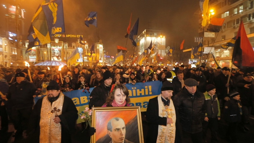 A Ukrainian nationalist carries a portrait of Stepan Bandera, founder of the Ukrainian rebel army that fought against the Soviet regime, during a rally in downtown Kiev, Ukraine, late Wednesday, Jan. 1, 2014. The rally was organized on the occasion of Bandera's birth anniversary.(AP Photo/Efrem Lukatsky)