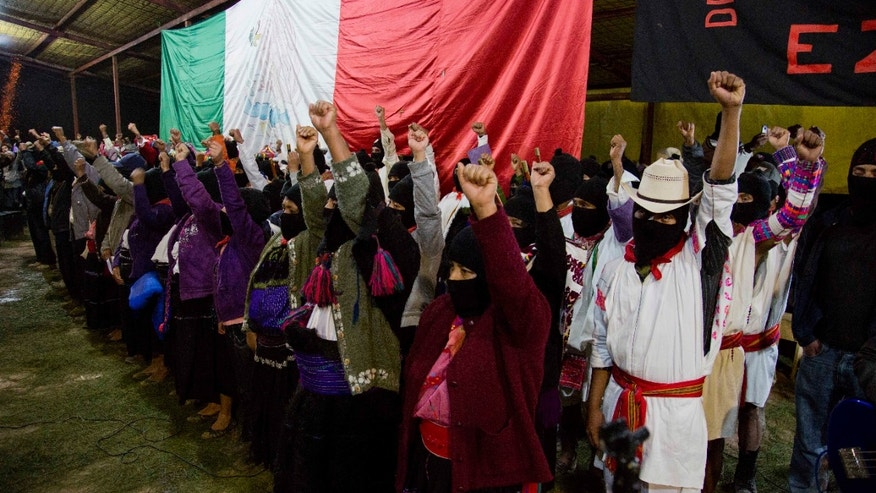 Masked members of the Zapatista National Liberation Army, EZLN, raise their fists during an event marking the 20th anniversary of the Zapatista uprising in the town of Oventic, Chiapas, Mexico, late Tuesday, Dec. 31, 2013. The revolt led Mexico to amend its constitution in 2001 to enshrine Indian rights, but the Zapatistas were enraged when lawmakers watered down the protections before approving them. (AP Photo/Eduardo Verdugo)