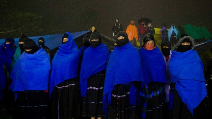 Masked women from the Zapatista National Liberation Army, EZLN, stand at attention during an event marking the 20th anniversary of the Zapatista uprising in the town of Oventic, Chiapas, Mexico, late Tuesday, Dec. 31, 2013. The rebellion stunned Mexico and drew widespread support from leftists across the world. But little has changed in the secretive, closed-off enclaves the Zapatistas have formed over the last two decades in the half-dozen communities they hold. (AP Photo/Eduardo Verdugo)