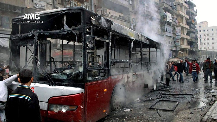This citizen journalism image provided by Aleppo Media Center AMC which has been authenticated based on its contents and other AP reporting, shows Syrians inspecting a burnt bus after a missile fired by Syrian government aircraft hit the vehicle in the rebel-held neighborhood of al-Bab in Aleppo, Syria, Tuesday, Dec. 31, 2013. The bus was full of people when it was struck, setting it on fire and killing several people, activists said.. (AP Photo/Aleppo Media Center AMC)