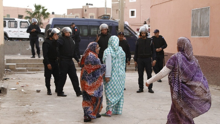 In this photo taken Tuesday, Dec. 10, 2013, Western Saharan women confront riot police in Laayoune, the capital of the disputed territory of the Western Sahara. Nearly 40 years after Morocco annexed these lands unemployment runs high and there are fears that the unrest and dissatisfaction could spill over into the unstable desert lands nearby where al-Qaida holds sway. (AP Photos/Paul Schemm)