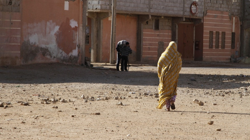 In this photo taken Thursday, Dec. 12, 2013, a Sahrawi woman in traditional dress walks through a low income neighborhood in Laayoune, the capital of the Western Sahara which has few jobs and needs investment. Nearly 40 years after Morocco annexed these lands unemployment runs high and there are fears that the unrest and dissatisfaction could spill over into the unstable desert lands nearby where al-Qaida holds sway.  (AP Photo/Paul Schemm)