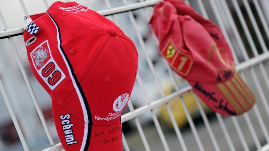 "Schumacher fan caps are attached on the fence at the Michael Schumacher Cart Center in his home town Kerpen, western Germany, Thiursday, Jan. 2, 2014. The Formula One record world champion is still in a coma after his skiing accident in France. Handwriting on the left cap reads ""We pray for you"". (AP Photo/dpa, Marius Becker)"