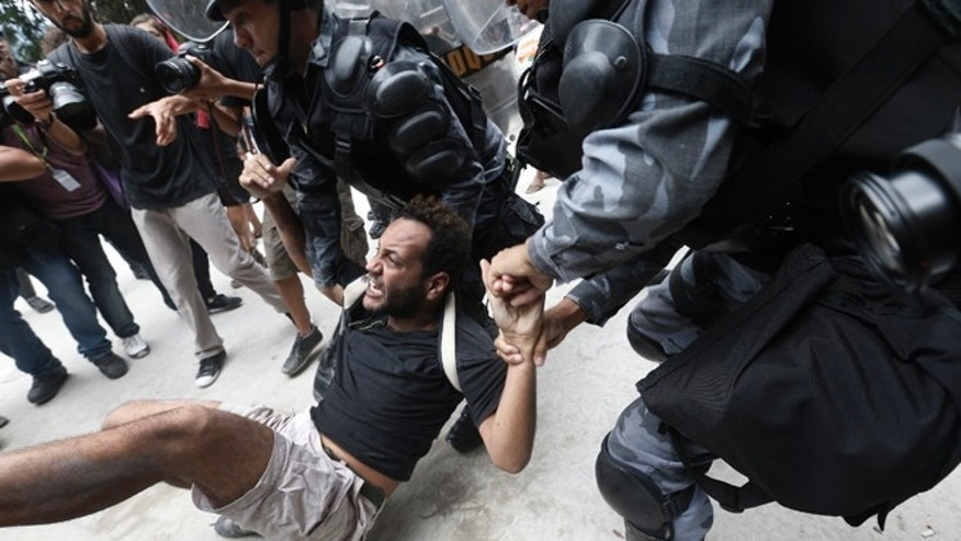 A man is carried away during a protest next to the Maracana Stadium in Rio de Janeiro, on Dec. 16, 2013.