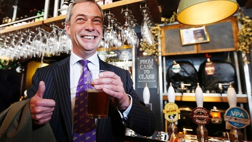 May 3, 2013: UK Independence Party (UKIP) leader Nigel Farage poses for a photograph with a pint of beer in the Marquis of Granby pub, in Westminster.