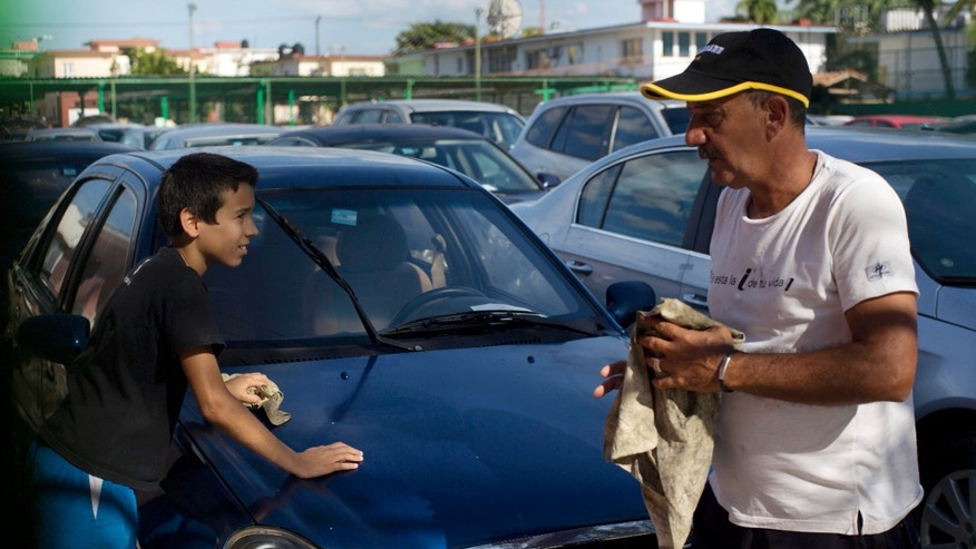 Jan. 2, 2014: A car dealership worker, right, and a boy clean a used Chinese Geely for sale at a government-run dealership in Havana, Cuba.