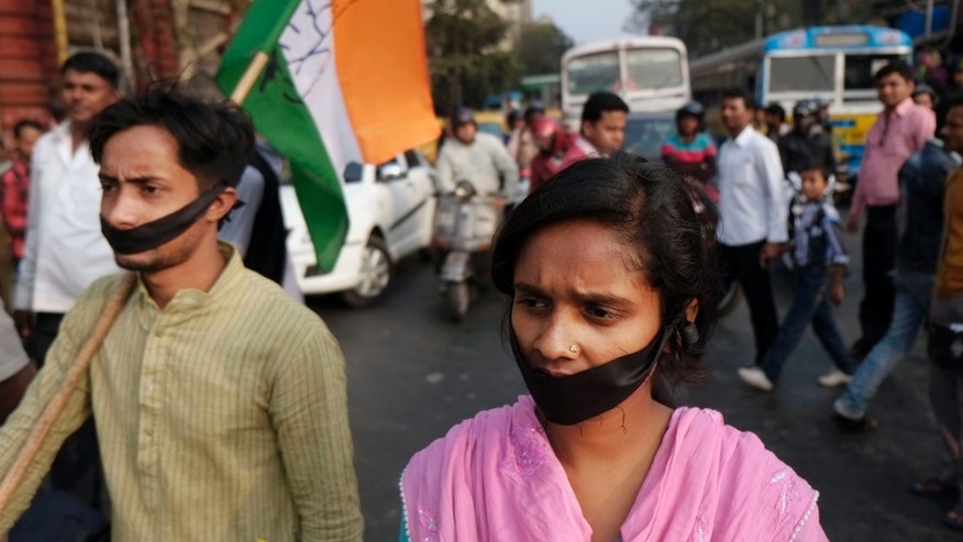 Activists of Indian National Congress with black bands around their mouth block traffic during a protest against a gang-rape and murder of a 16-year-old girl at Madhyamgram, about 25 kilometers (16 miles) north of Kolkata, India, Friday, Jan. 3, 2014. On Dec. 31 the girl set herself on fire and died due to burn injuries after being raped twice in October. The death of the girl has sparked outrage in the metropolis. (AP Photo/Bikas Das)