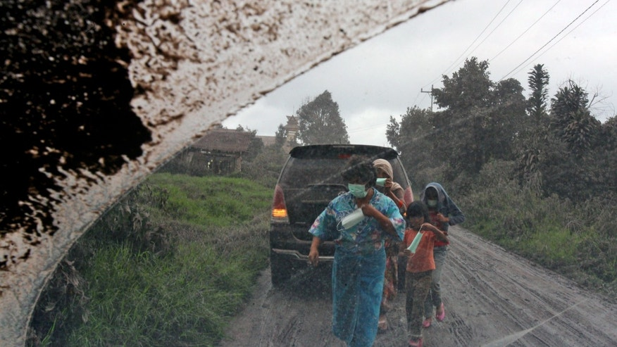 Villagers are seen through the windshield of a car as they seek cover during a volcanic ash fall from the eruption of Mount Sinabung in Tiga Pancur, North Sumatra, Indonesia, Saturday, Jan. 4, 2014. The 2,600-meter (8,530-foot) volcano has sporadically erupted since September. (AP Photo/Binsar Bakkara)