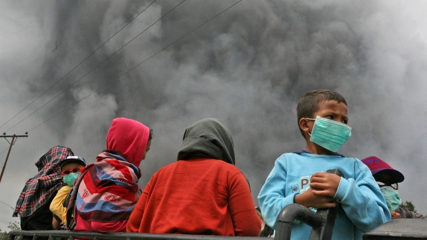 Villagers ride on a truck as volcanic ash from the eruption of Mount Sinabung is seen in the background in Beras Tepu, North Sumatra, Indonesia, Saturday, Jan. 4, 2014. The 2,600-meter (8,530-foot) volcano has sporadically erupted since September. (AP Photo/Binsar Bakkara)