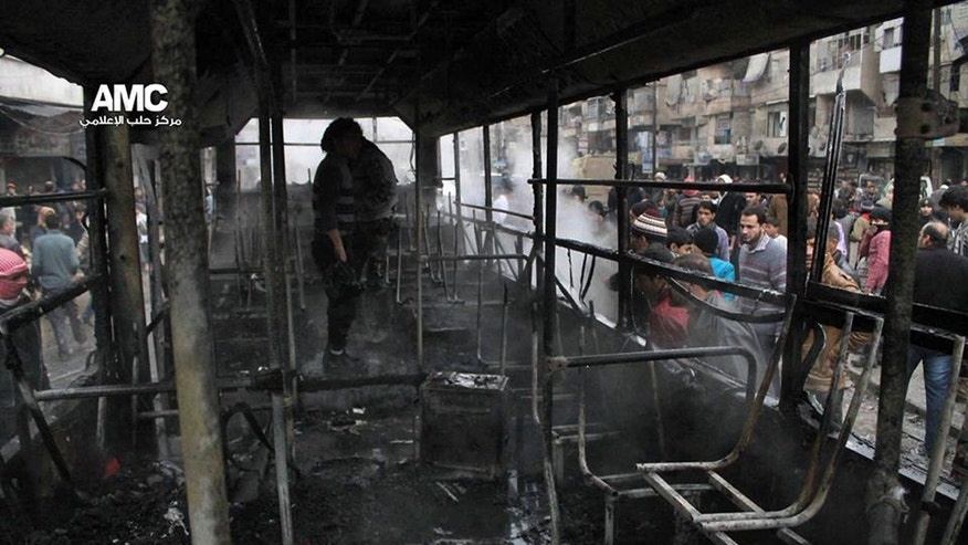 This image provided by Aleppo Media Center AMC which has been authenticated based on its contents and other AP reporting, shows Syrians inspecting a burnt bus after a missile fired by Syrian government aircraft hit the vehicle in the rebel-held neighborhood of al-Bab in Aleppo, Syria, Tuesday, Dec. 31, 2013. The bus was full of people when it was struck, setting it on fire and killing several people, activists said. (AP Photo/Aleppo Media Center AMC)