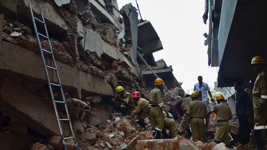 Rescue workers stand amid the debris of a building that collapsed in Canacona, a city about 70 kilometers (44 miles) from the state capital of Panaji, India, Saturday, Jan. 4, 2014. A five-story building under construction in the southern Indian state of Goa collapsed on Saturday, killing at least seven workers and leaving dozens more feared trapped under the rubble, police said. (AP Photo)