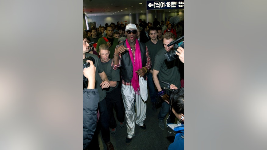 Former NBA basketball player Dennis Rodman, center, speaks as he is mobbed by media at the departure hall of Beijing International Capital Airport in Beijing Monday, Jan. 6, 2014. Rodman says he's going forward with an exhibition game including former NBA players in North Korea because he wants to connect with its people and let others know the sheltered communist country isn't so bad. (AP Photo/Andy Wong)