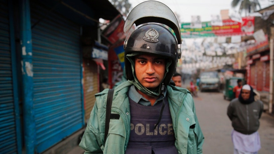 A Bangladeshi policeman watches as he stands guard on a street during a nationwide 48-hour strike called by the main opposition Bangladesh Nationalist Party (BNP) a day ahead of general elections in Dhaka, Bangladesh, Saturday, Jan. 4, 2014. The run-up to Sunday's general election in Bangladesh has been marked by bloody street clashes and caustic political vendettas, and the vote threatens to plunge this South Asian country even deeper into crisis. (AP Photo/Rajesh Kumar Singh)