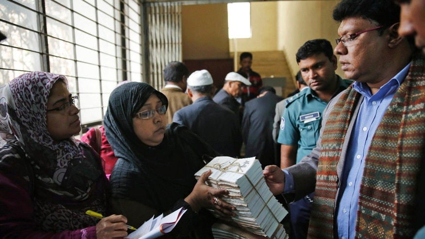 Bangladeshi election officials check ballot papers and other election materials at a distribution center a day before general elections in Dhaka, Bangladesh, Saturday, Jan. 4, 2014. The run-up to Sunday's general election in Bangladesh has been marked by bloody street clashes and caustic political vendettas, and the vote threatens to plunge this South Asian country even deeper into crisis. (AP Photo/Rajesh Kumar Singh)