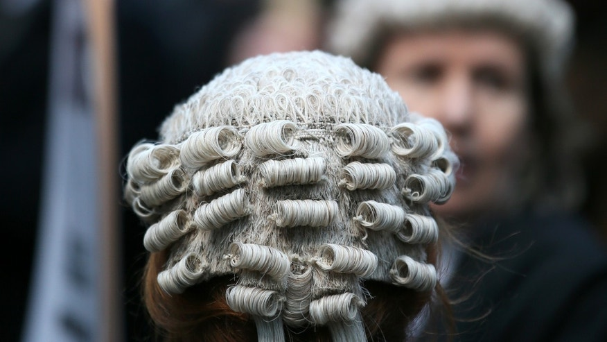 Lawyer Alice Jarratt takes part in a protest outside Southwark Crown Court during a demonstration against cuts to legal aid funding, in London, Monday, Jan. 6, 2014. Hundreds of British lawyers, many dressed in traditional wigs and gowns, have swapped courtrooms for picket lines to protest planned cuts to legal-aid funding. Hearings were disrupted Monday at courts including London's famous Old Bailey as barristers staged their first-ever national walkout. The British government, which has slashed spending in the name of deficit reduction, plans to cut lawyers' fees in a bid to reduce the legal aid budget by 220 million pounds ($360 million) by 2019.  (AP Photo/Alastair Grant)