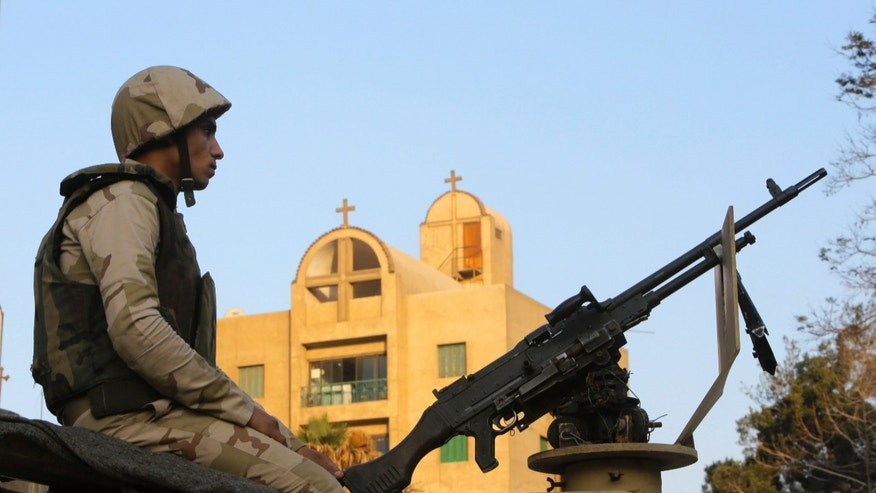 An Egyptian army soldier guards St. Mark Cathedral in Cairo, Egypt, Monday, Jan. 6, 2014 ahead of Coptic Christmas Eve mass. Egyptian authorities put up a heavy security cordon around the Coptic cathedral in Cairo hours before Christmas Eve mass, using bomb-sniffing dogs, metal detectors and officers. (AP Photo/Amr Nabil)