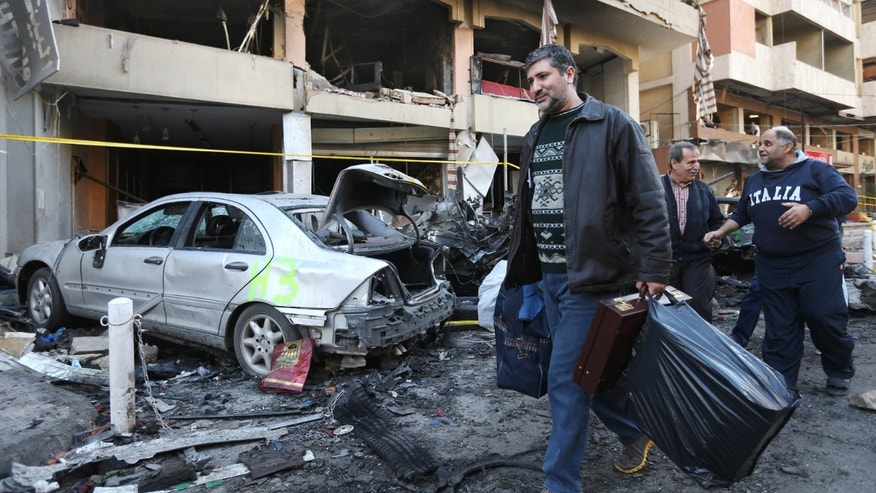 A Lebanese man carries his belongings as he leaves his damaged house at the site of an explosion in a stronghold of the Lebanese Shiite group Hezbollah in Beirut, Lebanon, Friday, Jan. 3, 2014. An explosion tore through a crowded commercial street Thursday in a south Beirut neighborhood that is bastion of support for the Shiite group Hezbollah, killing several people, setting cars ablaze and sending a column of black smoke above the Beirut skyline. (AP Photo/Hussein Malla)