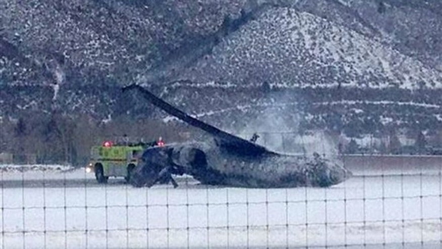 Emergency crews respond as a small plane lies on a runway at Aspen Airport in western Colorado after it crashed upon landing Sunday, Jan. 5, 2014. Emergency crews are responding to a fiery plane crash at Aspen Airport in western Colorado. (AP Photo/Corey Morris-Singer)