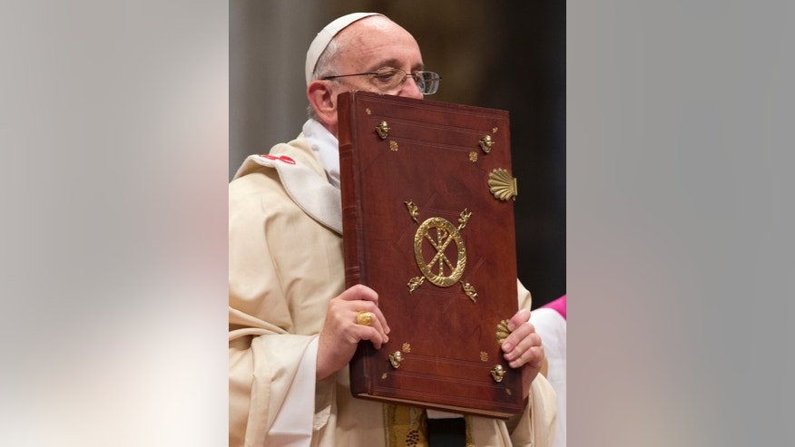 Pope Francis kisses the Holy Book as he celebrates a Mass in St. Peter's Basilica, at the Vatican, to mark Epiphany, Monday, Jan. 6, 2014. The Epiphany day, is a joyous day for Catholics in which they recall the journey of the Three Kings, or Magi, to pay homage to Baby Jesus. (AP Photo/Andrew Medichini)