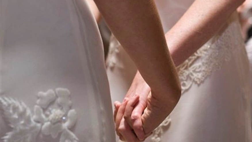 FILE - In this June 17, 2008 file photo, Amber Weiss and Sharon Papo, both of Berkeley, Calif., hold hands during their wedding ceremony at City Hall in San Francisco. What public schools will be required to teach about same-sex marriage has emerged as the central issue in the campaigns against same-sex marriage in both California and Maine.(AP Photo/Darryl Bush, FILE)