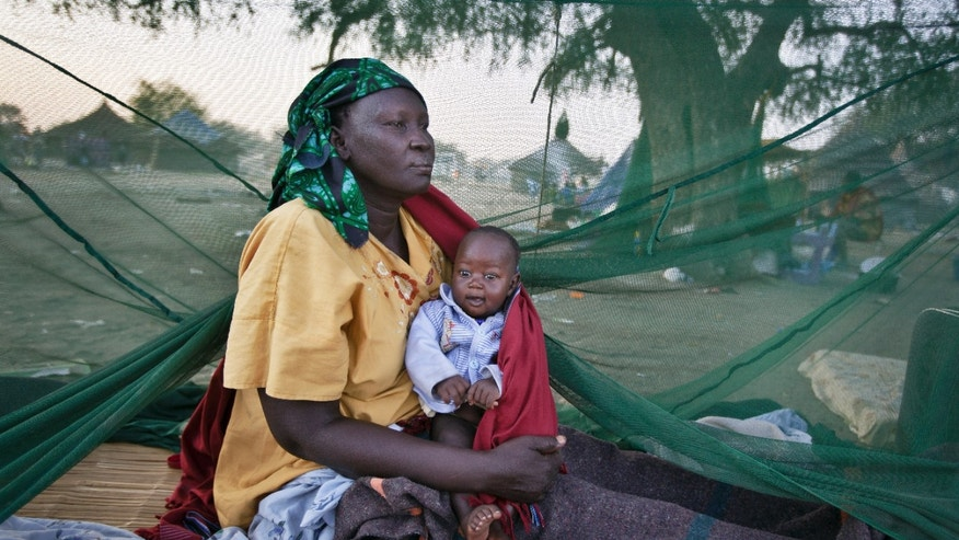 In this photo taken Thursday, Jan. 2, 2014, a displaced mother and her baby, one of the few to have a mosquito net, wake up in the morning after sleeping in the open, some of the thousands who fled the recent fighting between government and rebel forces in Bor by boat across the White Nile, in the town of Awerial, South Sudan. (AP Photo/Ben Curtis)