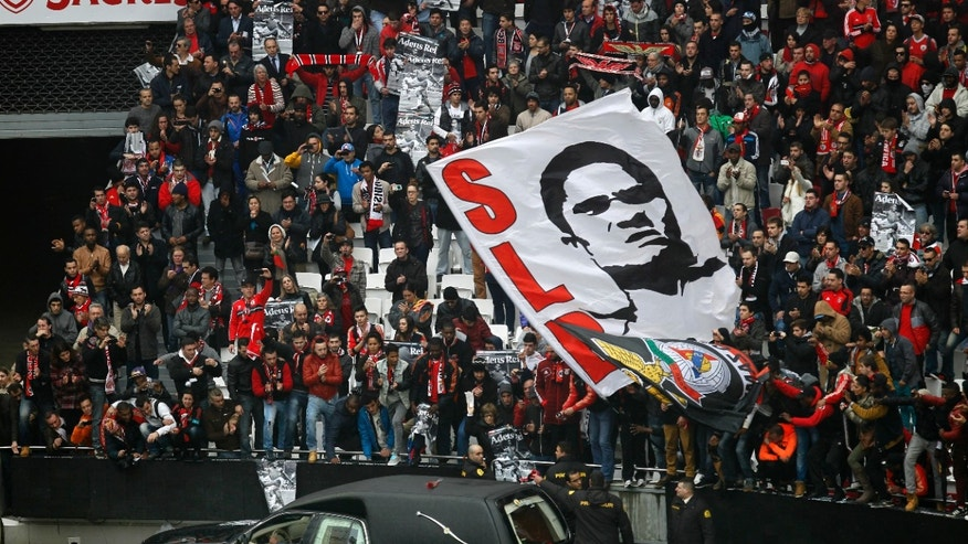 "The remains of the Portuguese soccer player legend Eusebio are carried inside a car as supporters cheer during his memorial tribute at the Benfica's Luz stadium in Lisbon, Monday, Jan. 6, 2014.  Eusebio, the Portuguese football star who was born into poverty in Africa but became an international sporting icon and was voted one of the 10 best players of all time, has died aged 71, his longtime club Benfica said. Few supporters hold posters with the photograph of Esusebio that read in Portuguese: ""Bye King"". (AP Photo/Francisco Seco)"