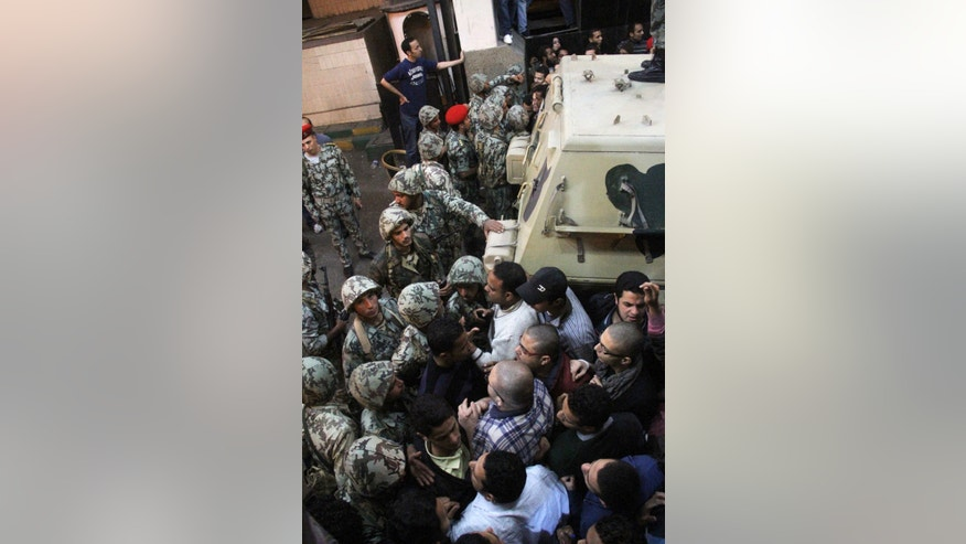 "FILE - In this file photo taken Saturday, March 5, 2011, Egyptian soldiers, left, are unsuccessful as they try to stop angry protesters who storm the state security building headquarters in Cairo's northern Nasr City neighborhood, Egypt. After a Dec. 2012 bombing hit a security headquarters in Mansoura in Egypt's Nile Delta, calls flooded into a hotline run by security agencies as people reported suspected members of the Muslim Brotherhood and activists accused of being ""traitors"" for breaching the offices of the state security agency. But perhaps more importantly, the security agency's hotline aims to enlist the broader public on its side as the agency widely hated during Mubarak's era tries to rehabilitate its image. (AP Photo/Ahmed Ali, File)"