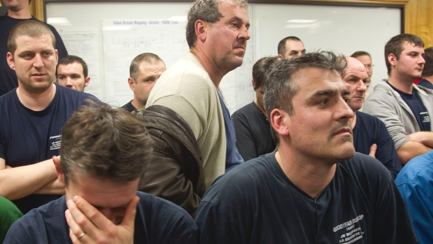 Workers of the Goodyear tire factory gather at the plant in Amiens, northern France, Monday, Jan. 6, 2014. Two Goodyear managers, production manager Michel Dheilly and Human Resources director Bernard Glesser, were blocked from leaving the plant on Monday, with angry workers demanding more money in exchange for the inevitable loss of their jobs. (AP Photo/Michel Euler)