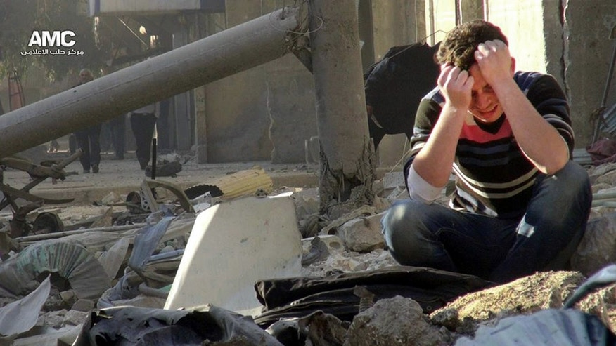 In this Monday, Dec. 23, 2013 citizen journalism image provided by Aleppo Media Center AMC, which has been authenticated based on its contents and other AP reporting, A Syrian man mourns as he sits in the rubble of buildings following a Syrian government airstrike in Aleppo, Syria. Government forces widened a bombing campaign in rebel-held areas of northern Syria on Monday, striking the northern city of Aleppo and a town on the Turkish border in raids that left an estimated 45 people dead, activists said. (AP Photo/Aleppo Media Center AMC)