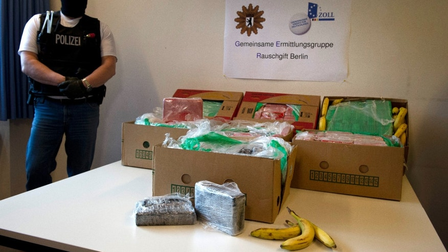 "A masked poliman stands next to banana crates with confiscated drugs in the police headquarters in Berlin, Tuesday Jan.7, 2014. Poster in center reads : Special Drug Investigation Group Berlin. Police say they have seized a large haul of cocaine after smugglers apparently made a mistake that saw the drugs end up in supermarkets. Workers at five stores in and around Berlin were surprised to find 140 kilograms (309 pounds) of cocaine packed into crates of bananas on Monday. The head of Berlin's anti-drugs squad said Tuesday that the crates had come from Colombia and the discovery was ""pure chance."" German news agency dpa quoted Olaf Schremm as saying that the smugglers had probably made ""a logistical mistake."" It's estimated that the drugs would have had a street value of about 6 million euro ($8.2 million).   (AP Photo/dpa, Daniel Naupold)"